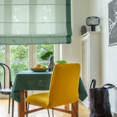 Large shopping bag next to a wooden table with a green tablecloth and a bowl of lemons in a natural kitchen and dining room interior