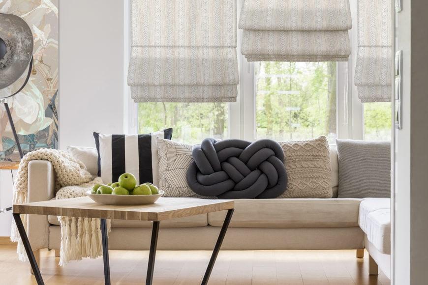 Cute pillows on white comfortable sofa in spacious modern living room