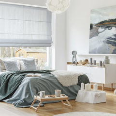 Green and blue bedsheets on bed in bedroom interior with painting on the wall and window